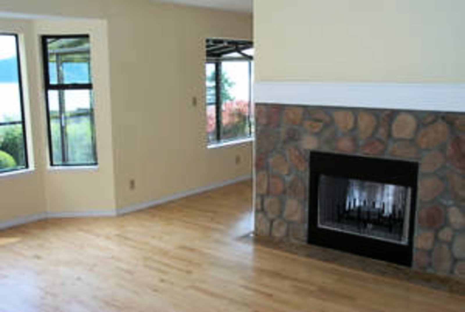 Living Room Birchwood floors with wood burning fireplace and ocean view.